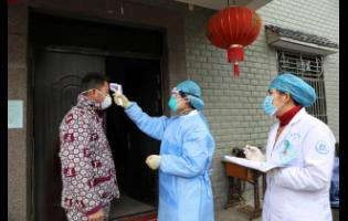 Community health workers check the temperature of a person who recently returned from Hubei Province, the centre of a virus outbreak, in Hangzhou in eastern China's Zhejiang Province, yesterday.