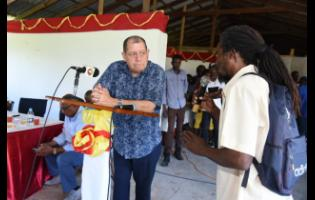 Agriculture minister Audley Shaw (left) listens to Donovan Taylor (right) during a meeting with sugar-cane farmers previously employed by the Golden Grove Sugar Factory in St Thomas last Friday.