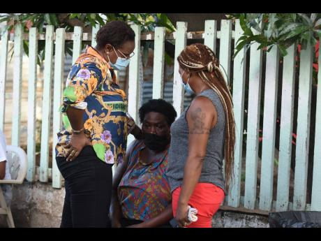A tearful Jacky (centre) has to be comforted by Venesha Phillips (left), councillor for the Papine division, and a family friend, after her two daugters were killed by gunmen in Mona Commons.